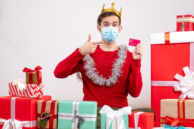 Front view young man with mask pointing at card sitting on floor xmas gifts