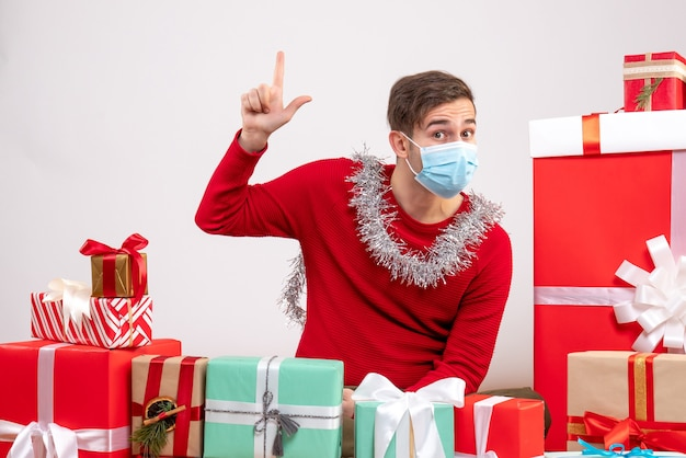 Front view young man with mask pointing at ceiling sitting around xmas gifts