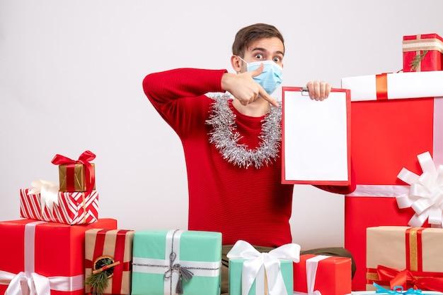 바닥 크리스마스 선물에 앉아 손가락 클립 보드 가리키는 마스크 전면보기 젊은 남자