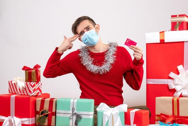 クリスマスプレゼントの周りに座っている彼の寺院に指銃を置くマスクを持つ正面図の若い男