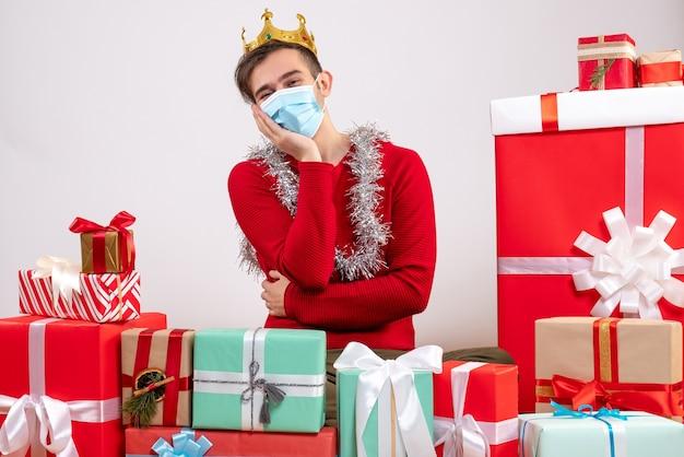 Giovane di vista frontale con la maschera che mette la mano sulla sua guancia che si siede sui regali di natale del pavimento