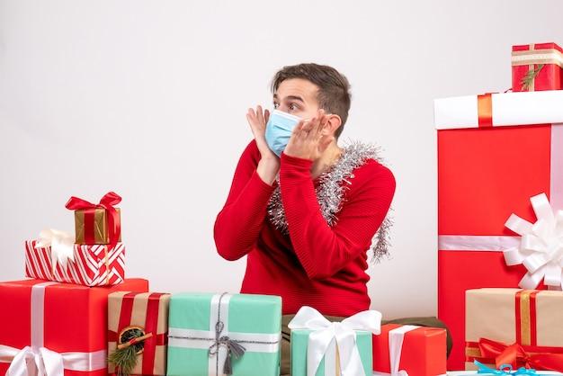 마스크 크리스마스 선물 주위에 앉아 그의 뺨에 손을 댔을 전면보기 젊은 남자