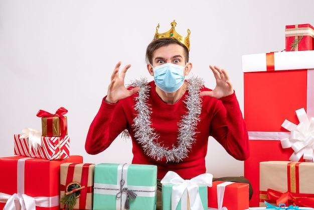 床に座っている怖いジェスチャーを示すマスクを持つ正面図の若い男クリスマスプレゼント