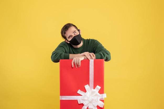 노란색에 큰 giftbox 뒤에 서있는 마스크와 전면보기 젊은 남자