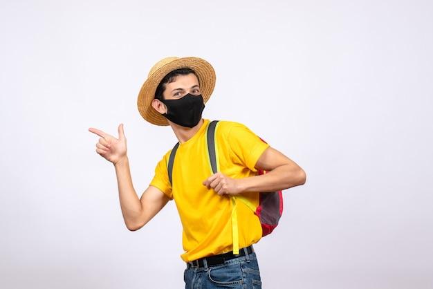 Giovane di vista frontale con maschera e maglietta gialla che indica qualcosa