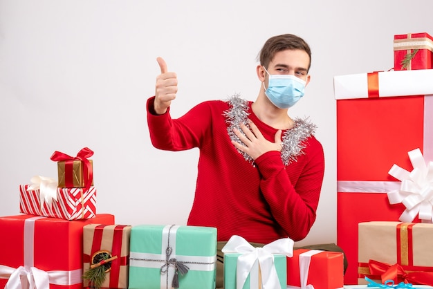 Front view young man with medical mask making thumb up sign sitting around xmas gifts