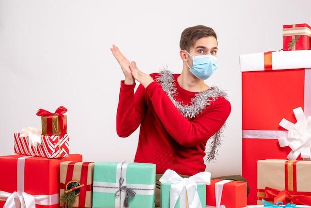 クリスマスプレゼントクリスマスの写真の周りに座っている医療マスクを持つ正面図の若い男