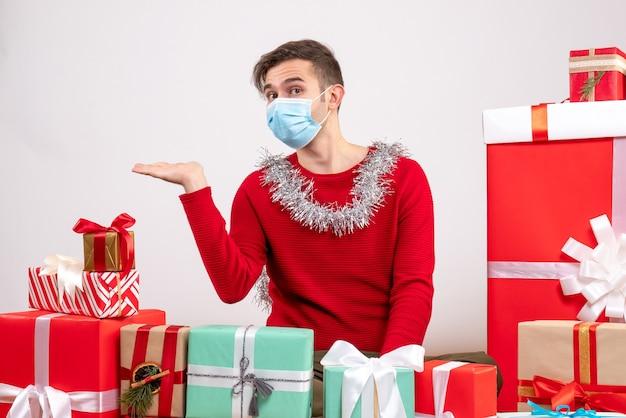 クリスマスプレゼントの周りに座っている医療マスクを持つ正面図の若い男