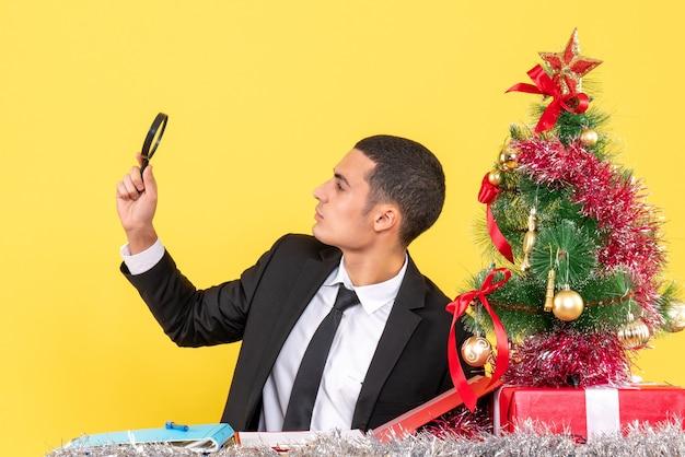테이블 크리스마스 트리와 선물에 앉아 손에 광학 루파와 전면보기 젊은 남자
