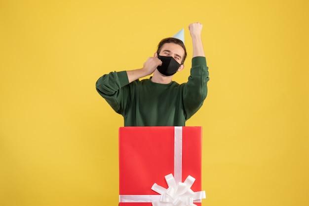 파티 모자와 노란색에 큰 Giftbox 뒤에 서있는 검은 마스크 전면보기 젊은 남자 무료 사진