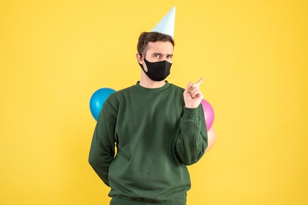 Вид спереди молодой человек с кепкой и разноцветными шарами, пряча воздушные шары за спиной, стоя на желтом