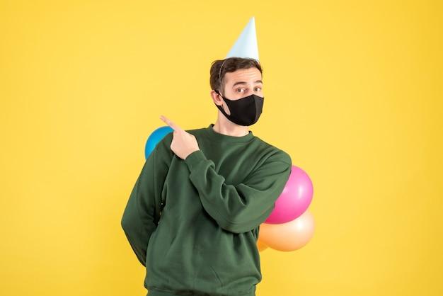 黄色の上に立っている彼の背中の後ろに彼の風船を隠しているパーティーキャップとカラフルな風船を持つ正面図の若い男