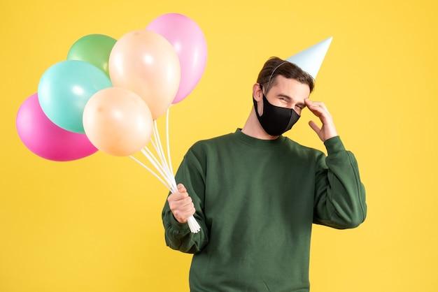 黄色の上に立っている頭を保持しているパーティーキャップとカラフルな風船を持つ正面図の若い男