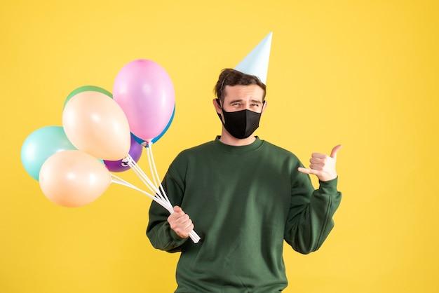 파티 모자와 노란색에 전화를 만드는 다채로운 풍선 전면보기 젊은 남자