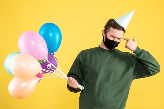 黄色の上に立っている彼の寺院に指銃を置くパーティーキャップとカラフルな風船を持つ正面図の若い男