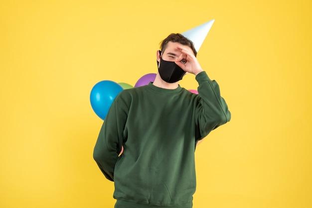 黄色の上に立っている彼の目の前にオーケーサインを置くパーティーキャップとカラフルな風船を持つ正面図の若い男