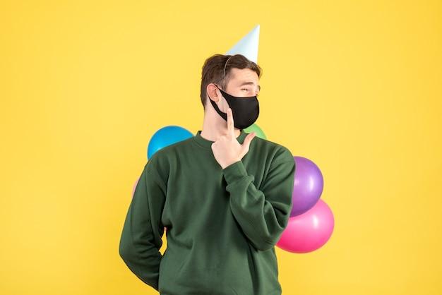 黄色の背景の自由な場所に立っているパーティーキャップとカラフルな風船と正面図の若い男