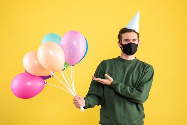 黄色の背景に立っているパーティーキャップとカラフルな風船と正面図の若い男