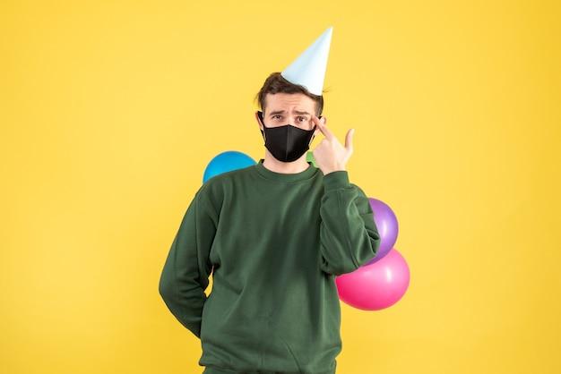 Вид спереди молодой человек с кепкой и разноцветными воздушными шарами, стоящий на желтом фоне