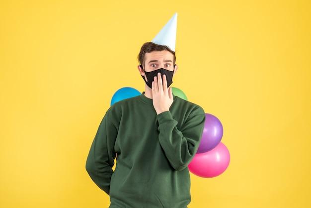파티 모자와 노란색 배경에 서있는 다채로운 풍선 전면보기 젊은 남자