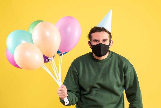 黄色の上に立っているパーティーキャップとカラフルな風船を持つ正面図の若い男
