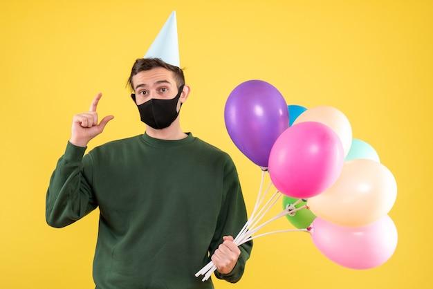 파티 모자와 노란색 배경에 검은 마스크를 쓰고 다채로운 풍선 전면보기 젊은 남자
