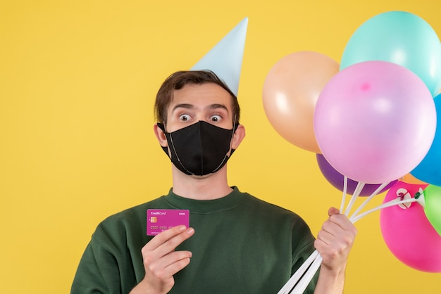 Front view young man with party cap and black mask holding card and balloons on yellow