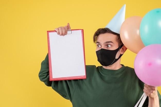 Giovane di vista frontale con cappuccio del partito e maschera nera che tiene appunti e palloncini su colore giallo