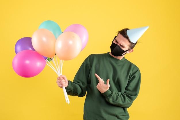 Giovane vista frontale con cappello da festa e maschera nera che punta a palloncini su giallo