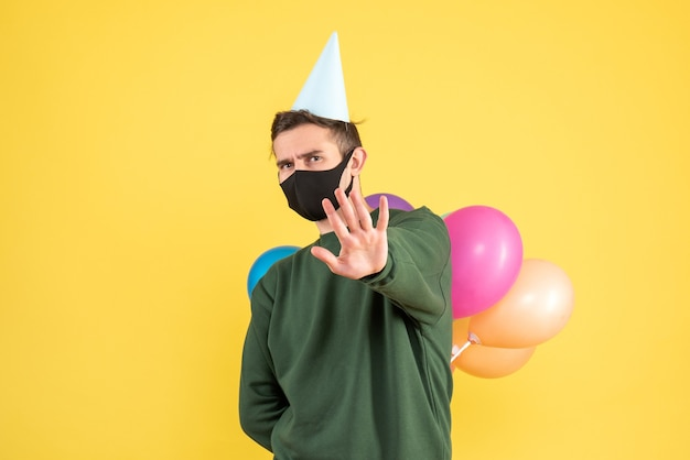 Front view young man with party cap and colorful balloons hiding balloons behind his back standing on yellow
