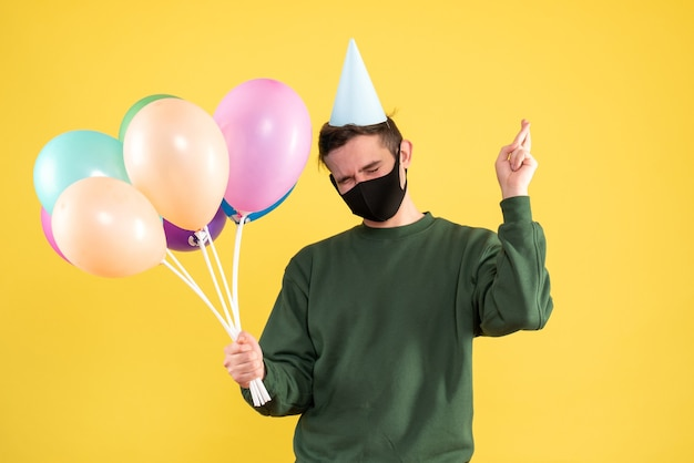 Front view young man with party cap and colorful balloons making good luck sign standing on yellow