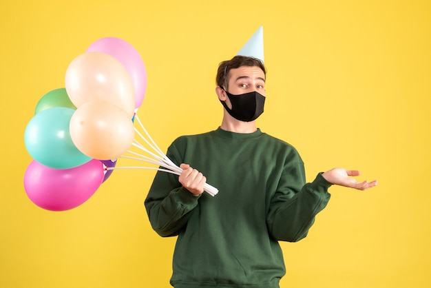 Giovane di vista frontale con cappuccio del partito e palloncini colorati che aprono la mano in piedi sul giallo