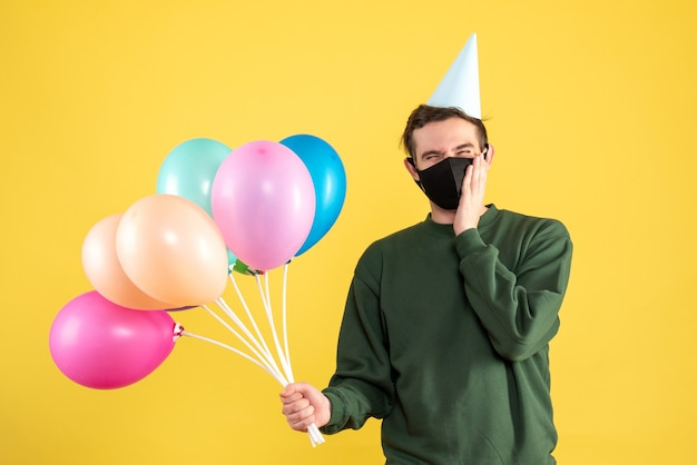 Front view young man with party cap and colorful balloons standing on yellow background