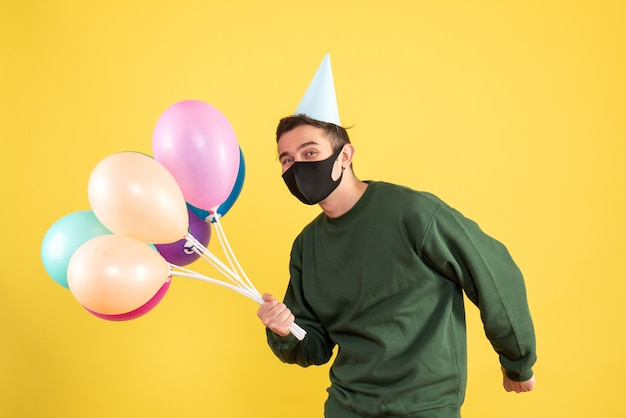 Front view young man with party cap and colorful balloons standing on yellow