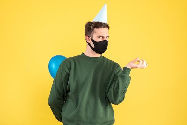 Giovane di vista frontale con cappuccio del partito e palloncini colorati in piedi sul giallo