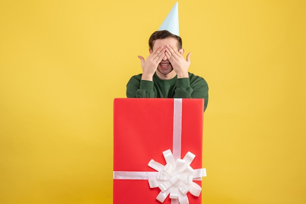Front view young man with party cap covering his eyes with hands standing behind big giftbox on yellow background