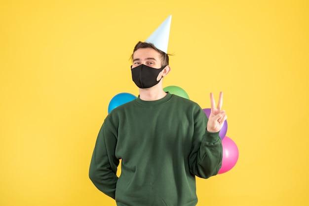노란색 배경에 그의 뒤 서 뒤에 풍선을 숨기고 파티 모자와 전면보기 젊은 남자