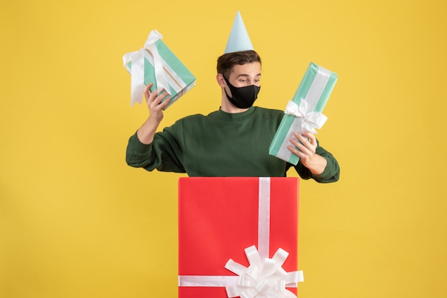黄色の背景の上の大きなギフトボックスの後ろに立っている贈り物を保持しているパーティーキャップを持つ正面図の若い男