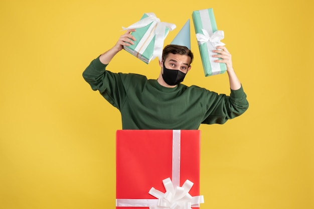 Front view young man with party cap holding gifts standing behind big giftbox on yellow background