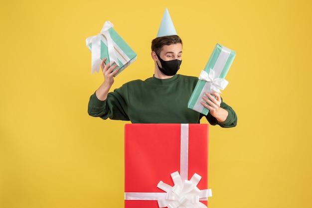 Giovane di vista frontale con il cappuccio del partito che tiene i regali che stanno dietro il grande giftbox su fondo giallo
