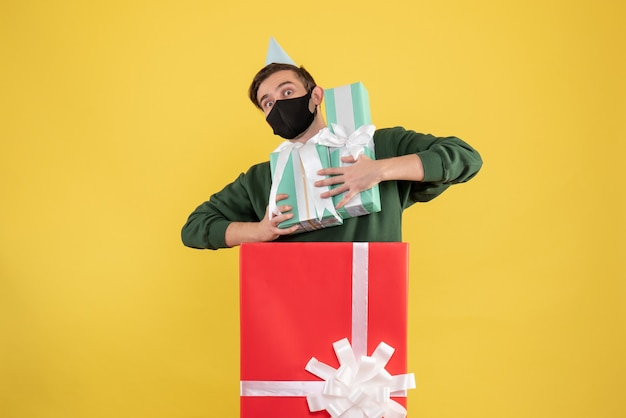 Front view young man with party cap holding xmas gifts standing behind big giftbox on yellow background