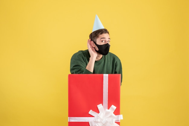 Front view young man with party cap listening at something standing behind big giftbox on yellow background