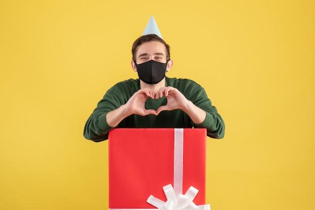 Вид спереди молодой человек в кепке, делая знак сердца с руками, стоящими за большой подарочной коробкой на желтом фоне