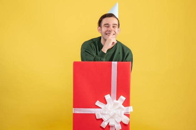 노란색 배경에 큰 giftbox 뒤에 서 쉿 기호를 만드는 파티 모자와 전면보기 젊은 남자
