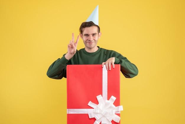 Вид спереди молодой человек в кепке делает знак победы, стоящий за большой подарочной коробкой на желтом фоне