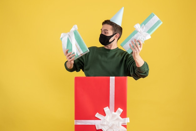 Front view young man with party cap and mask holding gifts standing behind big giftbox on yellow background