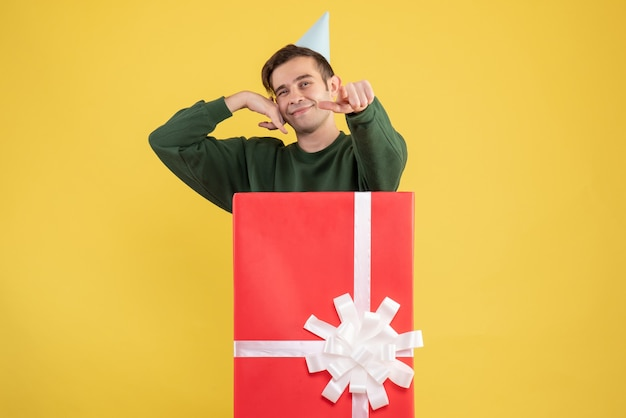 Front view young man with party cap pointing at camera standing behind big gift box on yellow background