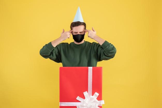 노란색 배경에 큰 giftbox 뒤에 서 그의 사원에 손가락을 넣어 파티 모자와 전면보기 젊은 남자