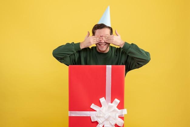 노란색 배경에 큰 giftbox 뒤에 서 그의 눈에 손을 댔을 파티 모자와 전면보기 젊은 남자
