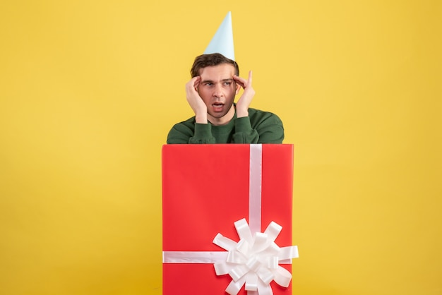 Front view young man with party cap standing behind big gift box on yellow background